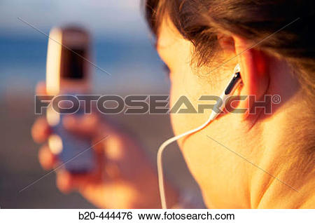Stock Images of 16 years old teenager listening to music in a MP3.