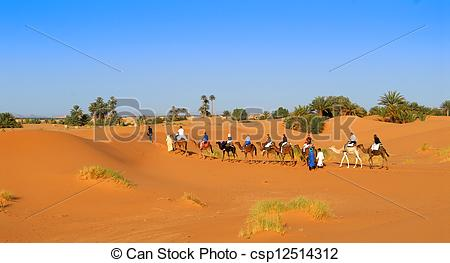 Stock Photography of Dromader caravan crossing red sands of Sahara.
