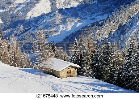 Pictures of Alpine hut in winter with roofs covered with a layer.