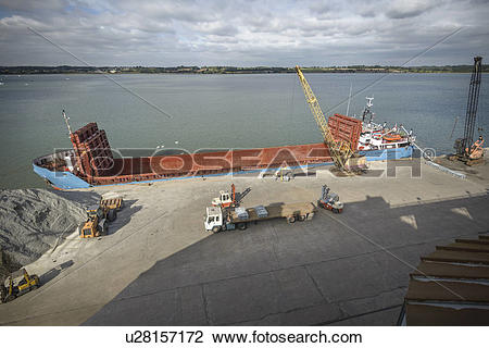 Stock Photo of High angle view of crane loading bulk cargo ship at.
