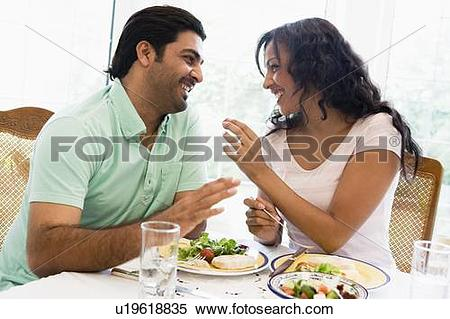 Stock Image of Couple sitting at dinner table smiling (high key.