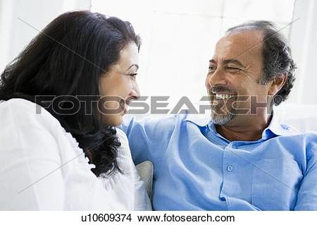 Stock Photo of Couple sitting in living room smiling (high key.
