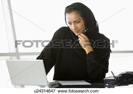 Picture of Businesswoman in office with laptop thinking (high key.