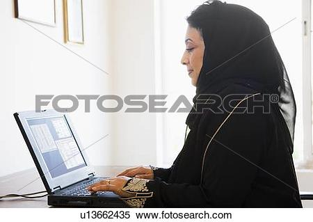 Stock Image of Woman in office with laptop (high key/selective.