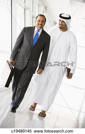 Stock Image of Two businessmen walking in corridor smiling (high.