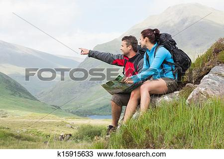 Stock Photo of Couple taking a break after hiking uphill and.