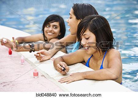 Stock Photography of Hispanic teenaged girls painting fingernails.