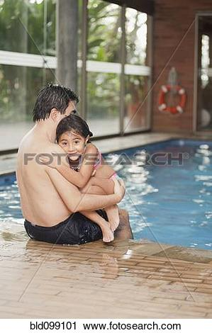 Stock Photography of Hispanic father and daughter sitting on edge.