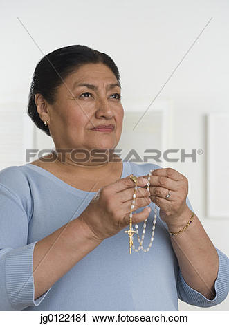Stock Photo of Senior Hispanic woman praying with rosary jg0122484.