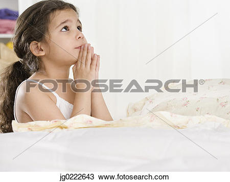 Stock Photo of Young Hispanic girl saying bedtime prayers.