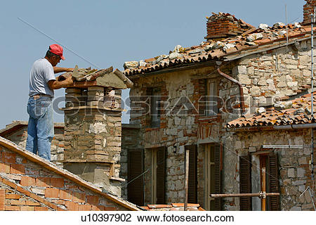 Stock Photo of Man mending chimney on roof in medieval historic.