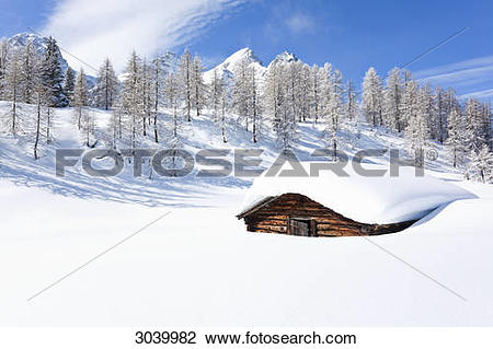 Stock Photo of hay hat on snow covered mountain pasture at the.