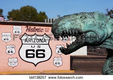 Picture of Close up of dinosaur statue by Historic Route 66 sign.