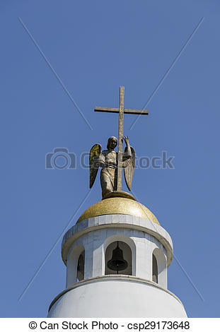 Stock Photo of Holy statue of carved winged angel with cross in.