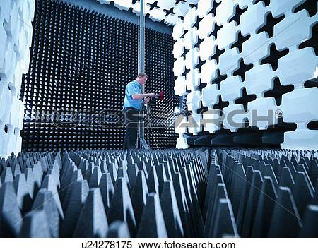 Stock Image of Engineer in anechoic chamber with horn antenna set.