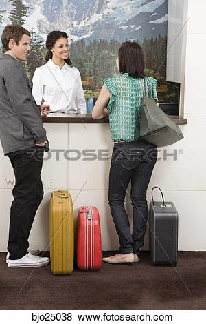 Pictures of Couple standing at hotel front desk bjo25038.