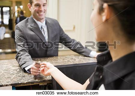 Stock Image of Businessman paying at hotel front desk ren03035.