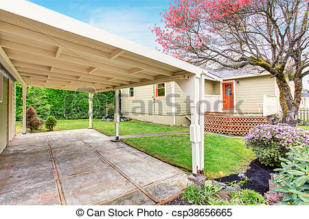 Stock Image of Old one story house with patio and fenced backyard.