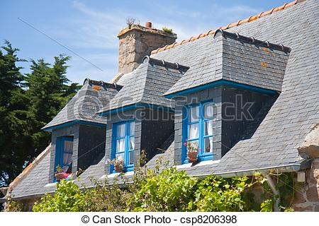 Pictures of Breton house with typical dormers and shutters, France.