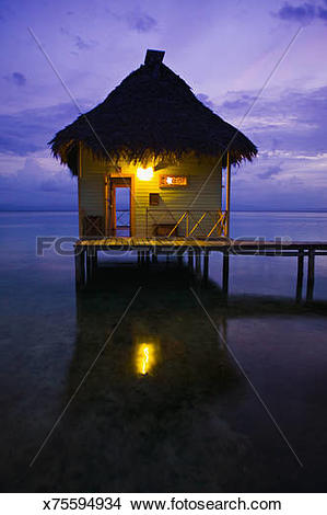 Stock Photo of Thatch roofed hut at end of dock, dusk x75594934.