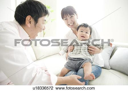 Stock Photo of Father tickling son's feet, son sitting on mother's.