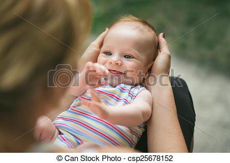 Stock Images of Adorable smiling baby held in his mother's lap.