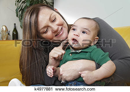 Stock Photography of Mixed race infanted smiles while seated on.