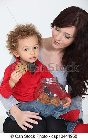 Stock Images of Cute child eating cookies on his mother's lap.