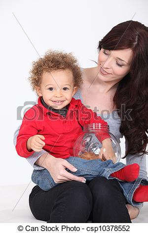 Stock Images of A cute kit eating cookie on his mother's lap.