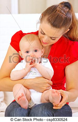 Stock Photo of Baby putting his hands in mouth while sitting on.