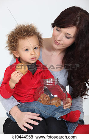Pictures of Cute child eating cookies on his mother's lap.
