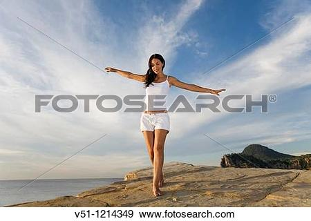 Stock Photograph of Brunette palyful woman in a cliff in Ibiza.