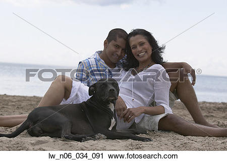 Stock Photography of Indian couple and dog sitting on beach.