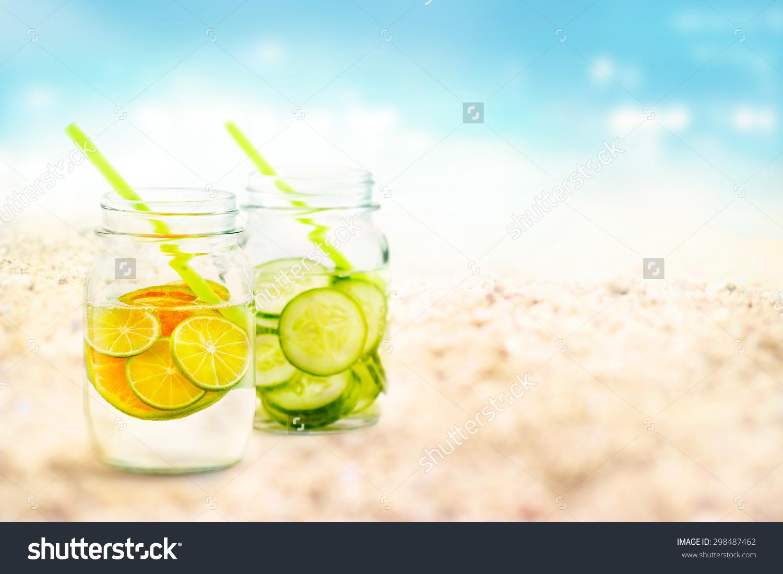 Infused Water Lemon And Cucumber In Mug On Sea Sand Beach Summer.