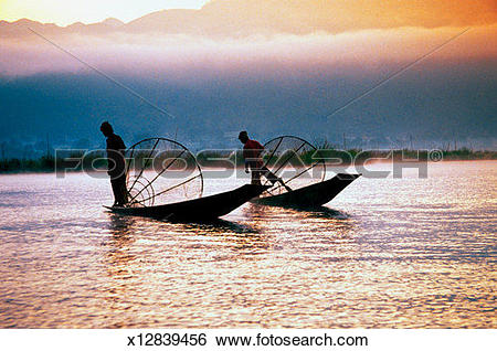 Stock Images of Silhouette of two fishermen on Inle Lake, Myanmar.