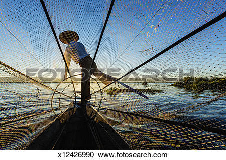 Stock Photography of Fisherman paddling his canoe on Inle Lake.