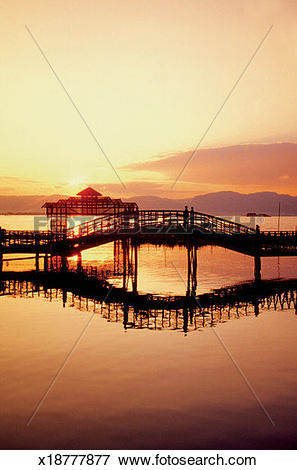 Picture of Silhouette of an arched bridge over Inle Lake at sunset.