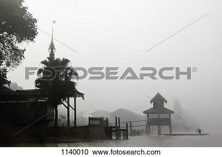 Stock Photography of Fog surrounding a village on Inle Lake, Burma.
