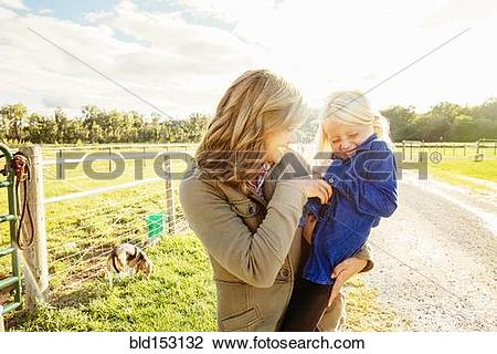 Stock Photo of Caucasian mother tickling daughter on rural road.