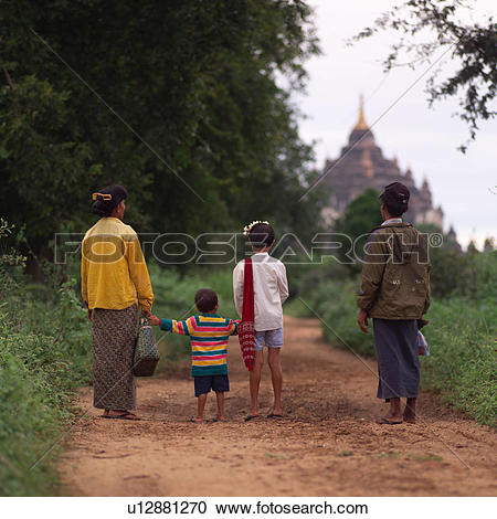 Stock Photography of Burmese family standing on a path looking at.