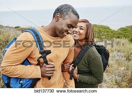 Stock Photography of Black couple hiking on rural hillside.