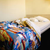 Stock Photo of Interior shot of motel room with unmade bed and.