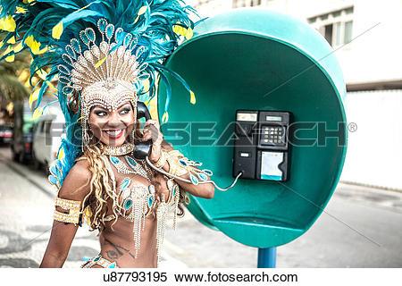 Stock Image of Samba dancer using pay phone, Ipanema Beach, Rio De.