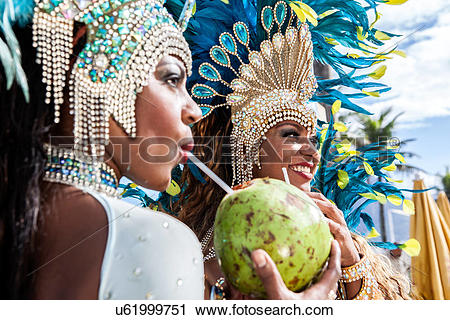 Stock Photography of Samba dancers in costume, drinking coconut.