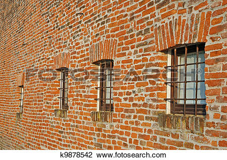 Stock Photo of red brick wall with iron lattice window of an farm.