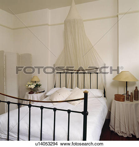 Stock Photo of White moxsquito bet above black iron bed with white.