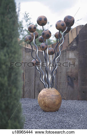 Stock Photo of Modern wood and metal sculpture in town garden.