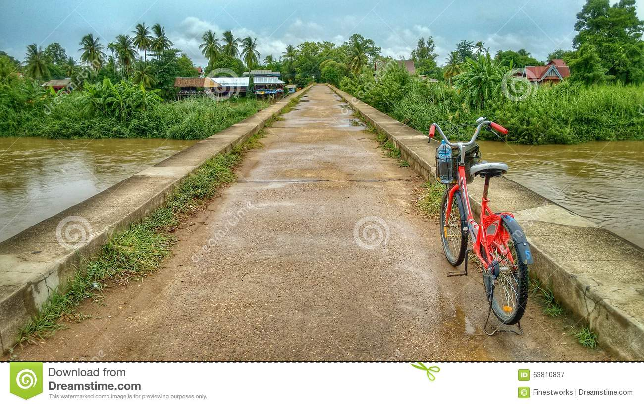 Red Bicycle On A Concrete Bridge Over The River Mekong In The.