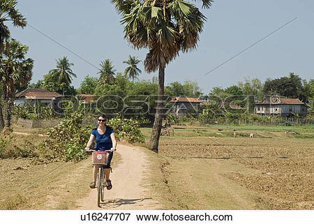 Picture of Woman pedaling her bike along the trails of Koh Trong.