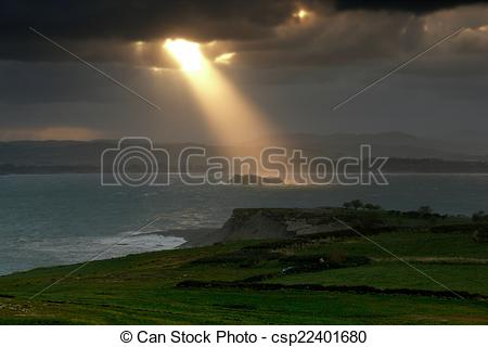 Pictures of Magical sunbeam over the island lighthouse.